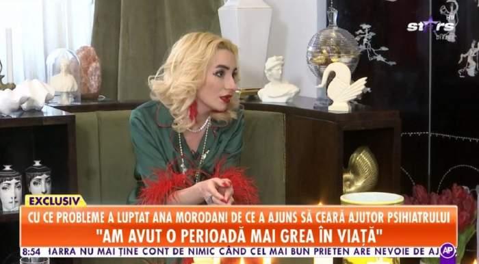 Ana Morodan oferă un interviu pentru Antena Stars. Vedeta poartă o bluză verde cu mâneci roșii și privește în jos.