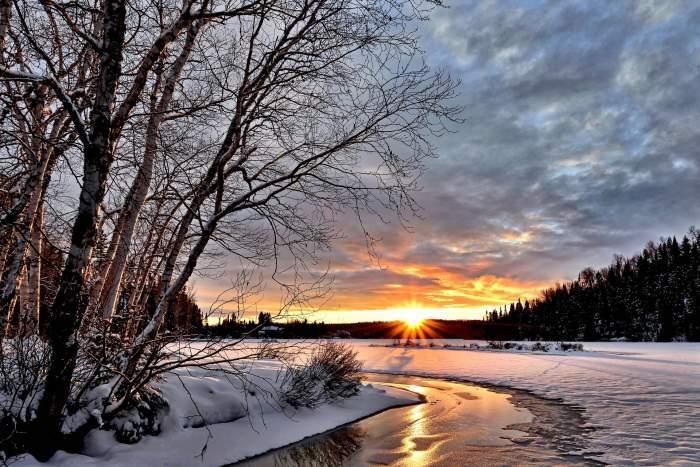 Imagine cu un peisaj din natura, acoperit de zapada, cu soarele care rasare