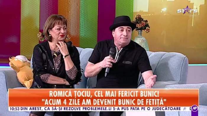 Romică Țociu și Adriana Trandafir se află pe canapeaua gri de la Star Matinal. El poartă pălărie și tricou negru, iar ea o bluză cu animal print și o alta neagră descheiată pe deasupra.