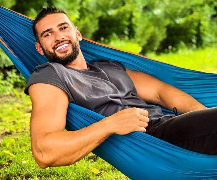Dorian Popa stă într-un hamac albastru. Artistul poartă un tricou gri, pantaloni negri și zâmbește.