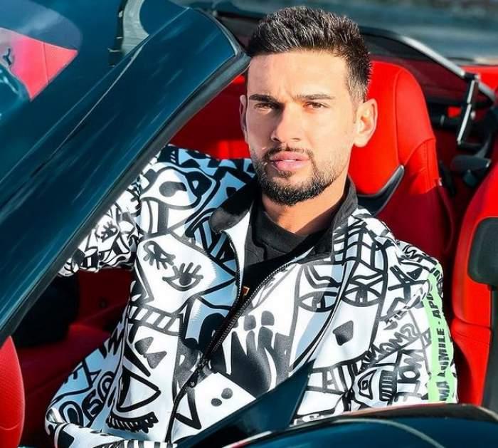 Dorian Popa se află într-o mașină decapotabilă cu tapițerie roșie. Artistul poartă un hanorac alb cu model negru.