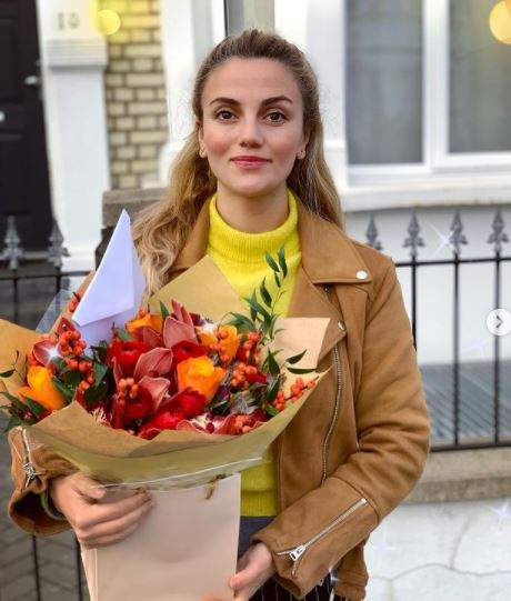 Selena cu un buchet de flori în brațe.