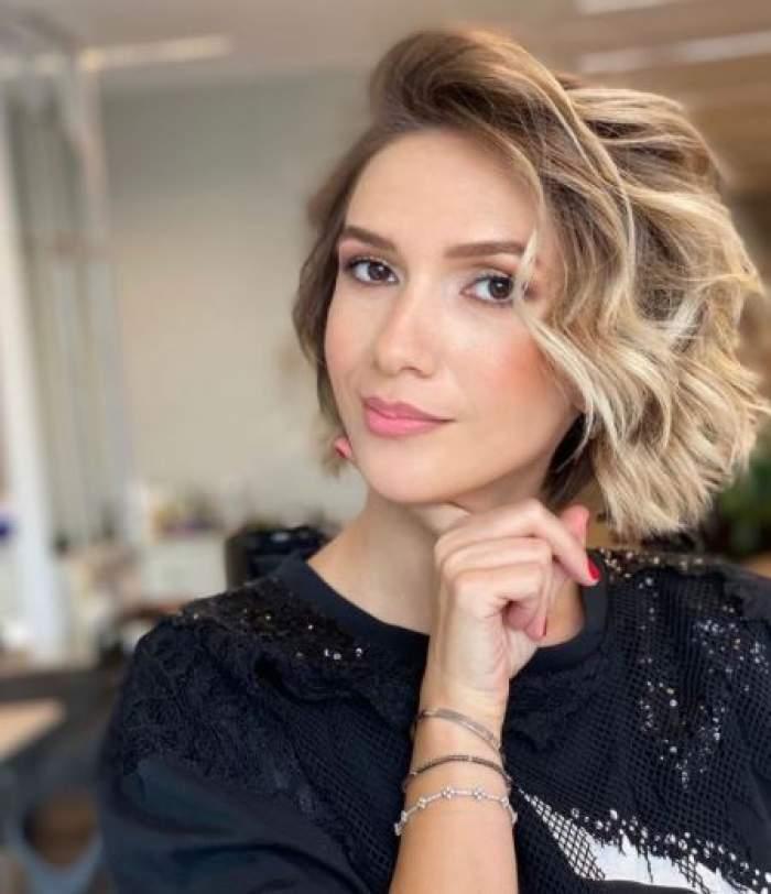 Adela Popescu cu bluză neagră și părul ondulat.