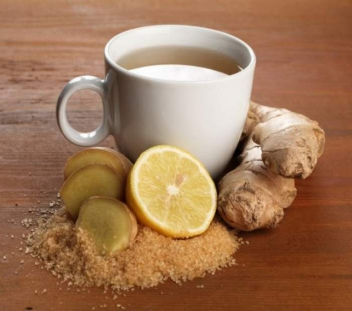 O cană de ceai cu lămâie lângă, scorțișoară și ghimbir