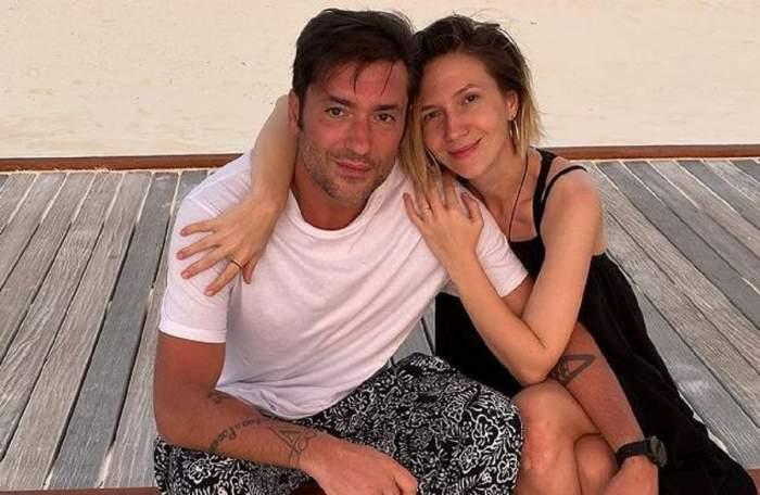 Adela Popescu și Radu Vâlcan stau pe un ponton gri. Ea își ține brațele în jurul spatelui său, iar ea pe piciorul ei. Artsta poartă o rochie neagră, iar prezentatorul un tricou alb și pantaloni negri cu model alb.