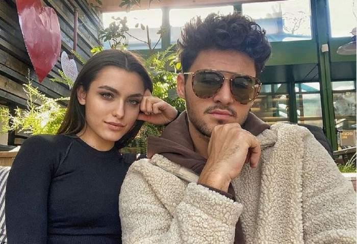 Mario Fresh și Alexia Eram se află la terasă. Ea poartă o bluză neagră și își ține cotul pe umărul lui, iar el ochelari de soare și o haină de iarnă crem și hanorac maro.