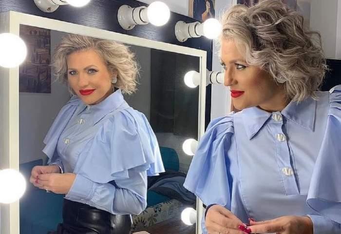 Mirela Vaida se uită în oglindă. Vedeta poartă o fustă neagră din piele și o cămașă bleu cu umeri voluminoși.