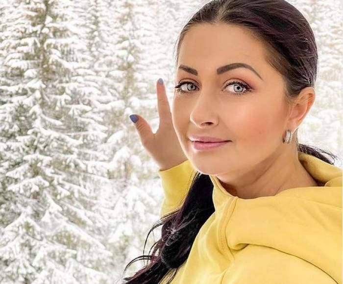 Gabriela Cristea ține mâna pe o fereastră. Pe geam se văd brazii ninși. Vedeta are părul prins în coadă și poartă un hanorac galben.