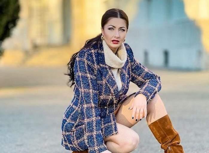 Gabriela Cristea se află pe stradă și e îmbrăcată cu un pardesiu abastru, pulover alb și o pereche de cizme maro. Vedeta stă pe vine și are gura întredeschisă.