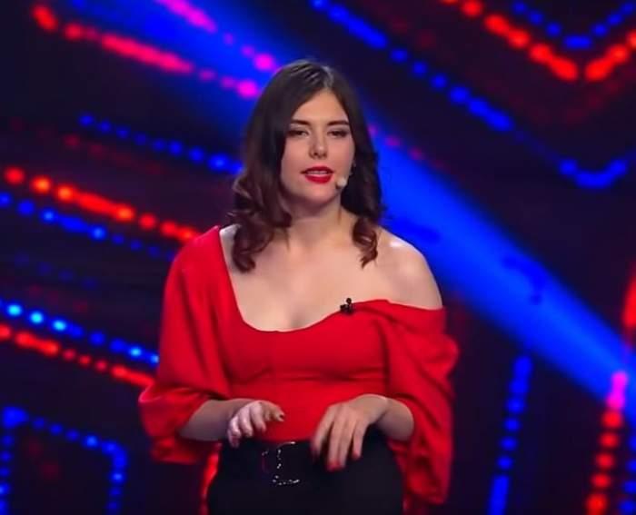 Ionela Irimescu e pe scena de la iUmor. Concurenta poartă pantaloni negri și bluză roșie.