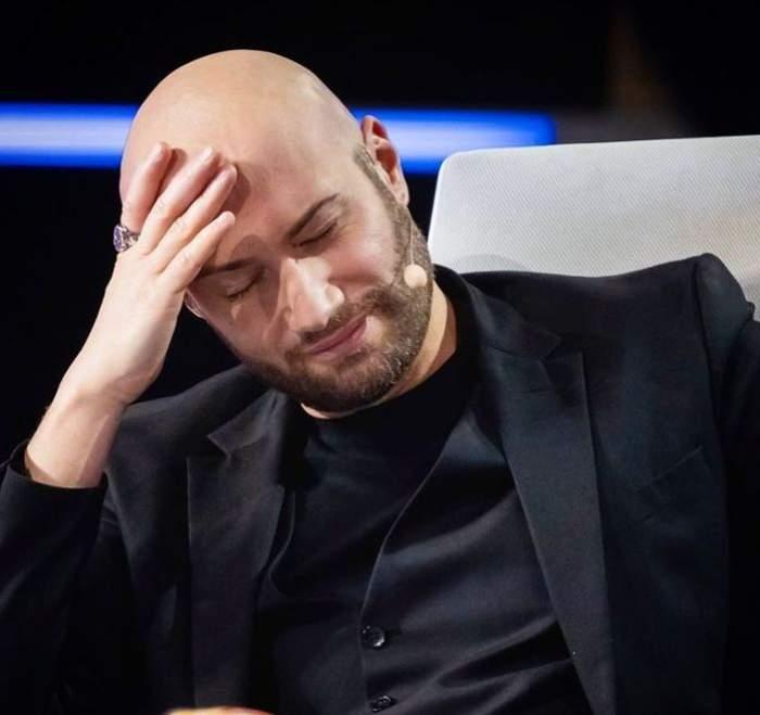 Mihai Bendeac se află la iUmor. Actorul poartă un costum negru și ține ochii închiși, având o mână pe cap.