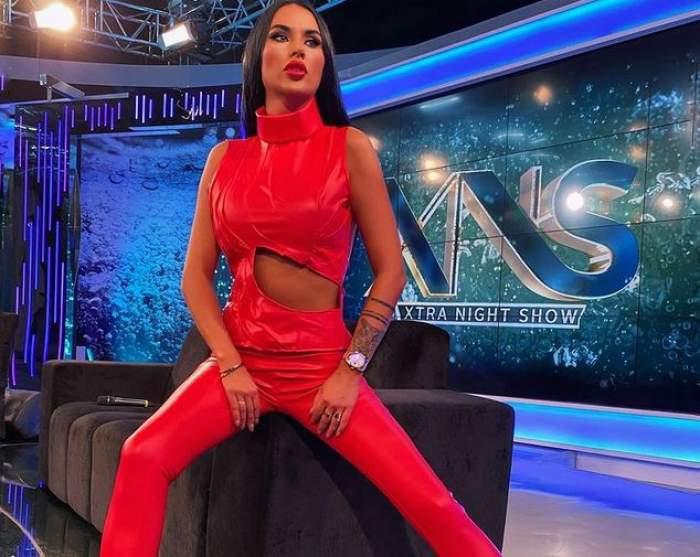 Daniela Crudu e în platou la Xtra Night Show. Vedeta stă pe o canapea neagră și poartă o salopetă roșie.
