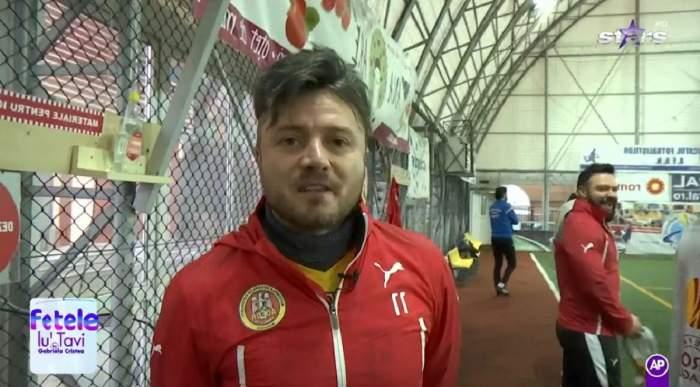 Tavi Clonda se află pe terenul de fotbal. Artistul poartă o bluză de trening roșie. În spatele lui se văd mai mulți jucători.