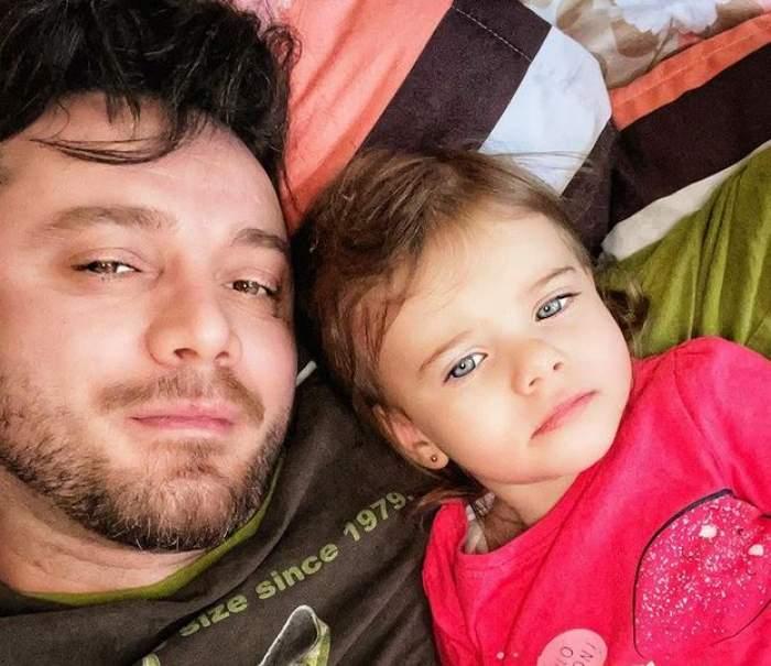 Tavi Clonda și fiica lui, Iris, stau în pat. El poartă un tricou maro, iar fetița unul roșu.