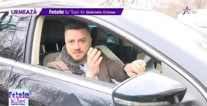 Tavi Clonda se află în mașină. Artistul poartă un tricou alb și o geacă maro.