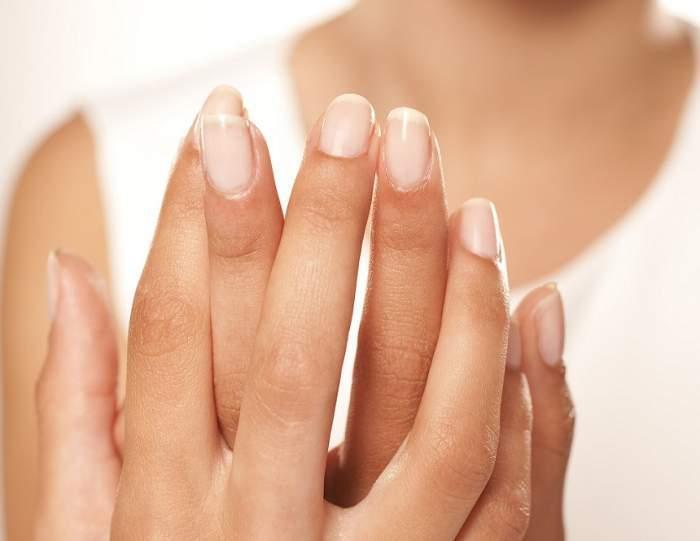 O femeie își arată unghiile perfecte, încrucișându-și mâinile