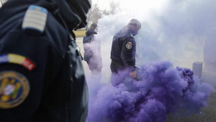 Polițiști în timp ce dau cu fumigene.