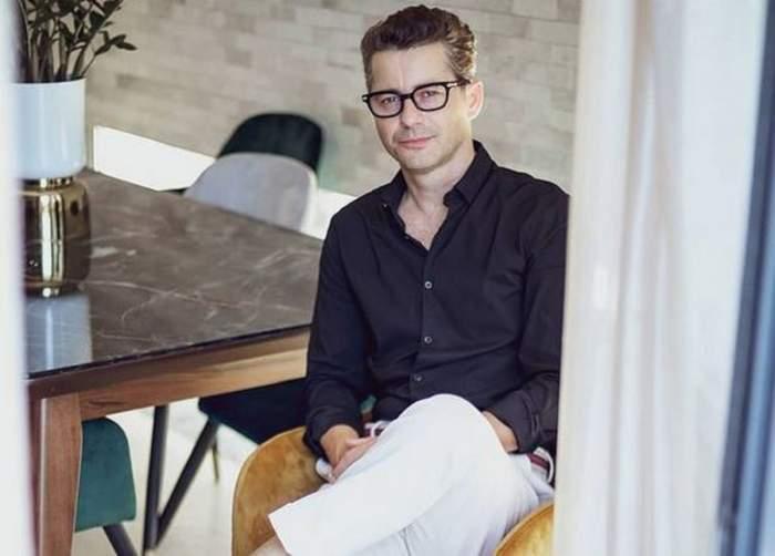 Adi Sînă stă pe scaun. Artistul poartă ochelari de vedere și e îmbrăcat cu o cămașă neagră și pantaloni albi. Vedeta ține picior peste picior.