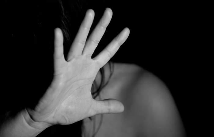 Imagine ilustrativa cu o femeie care se apara cu o mana