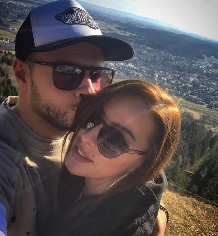 Lavinia Ilcău și iubitul într-un selfie. El o sărută pe obraz, iar ea poartă ochelari de soare și zâmbește larg. În spatele lor se vede o câmpie cu mai multe case.