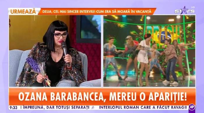 Ozana Barabancea stă pe canapeaua bleu de la Star Matinal. Vedeta ține microfonul și o zambilă mov în mână și poartă o bluză neagră, iar pe deasupra un sacou cu paiete colorate.