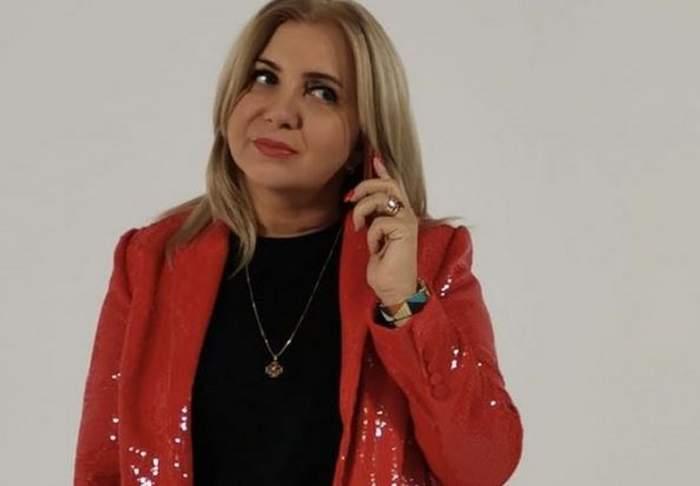 Carmen Șerban poartă o bluză neagră, iar pe deasupra un sacou roșu din material lucios. Vedeta ține un telefon roșu la ureche.
