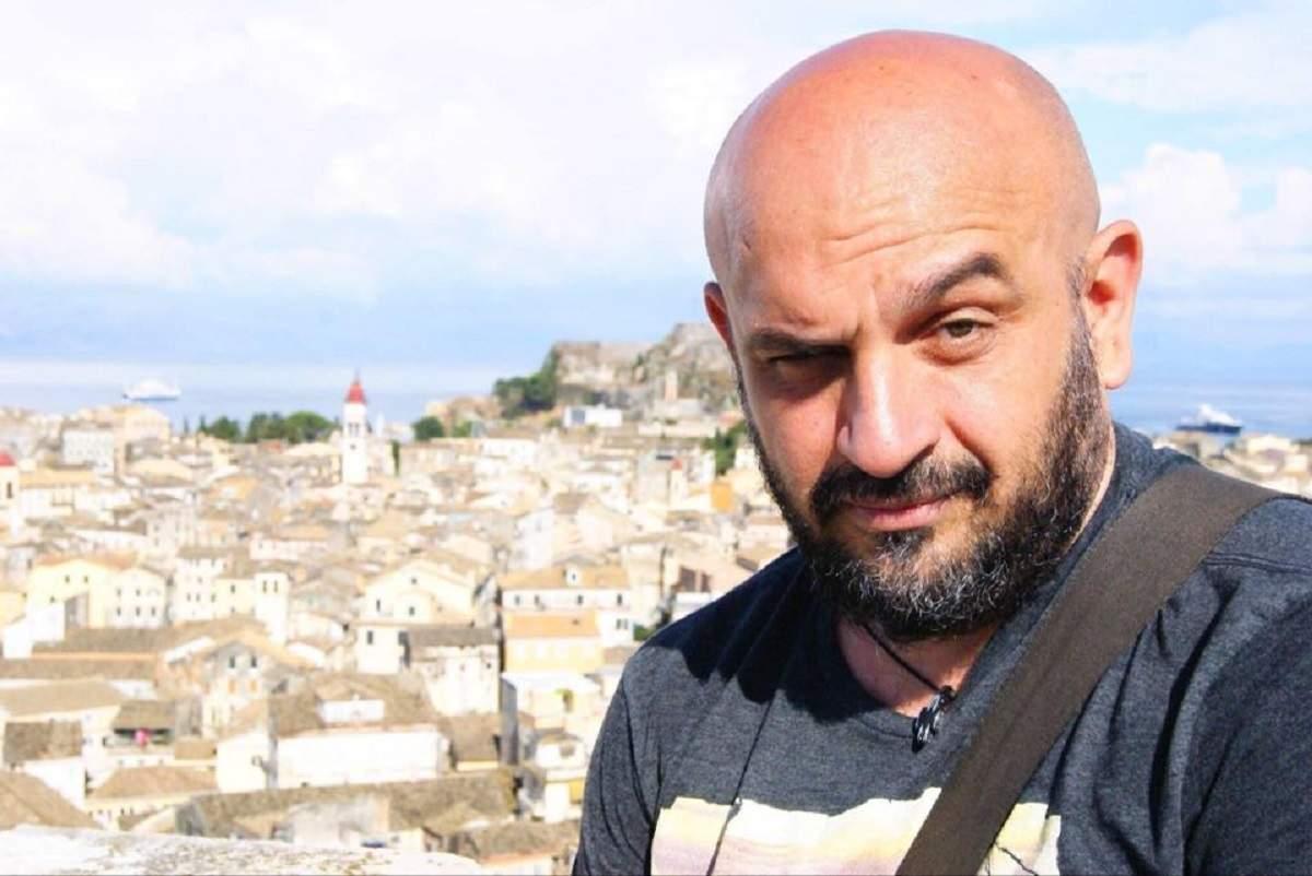 Alin Gălățescu își face un selfie. Criticul de modă poartă un tricou gri, iar în spatele lui se văd mai multe case.