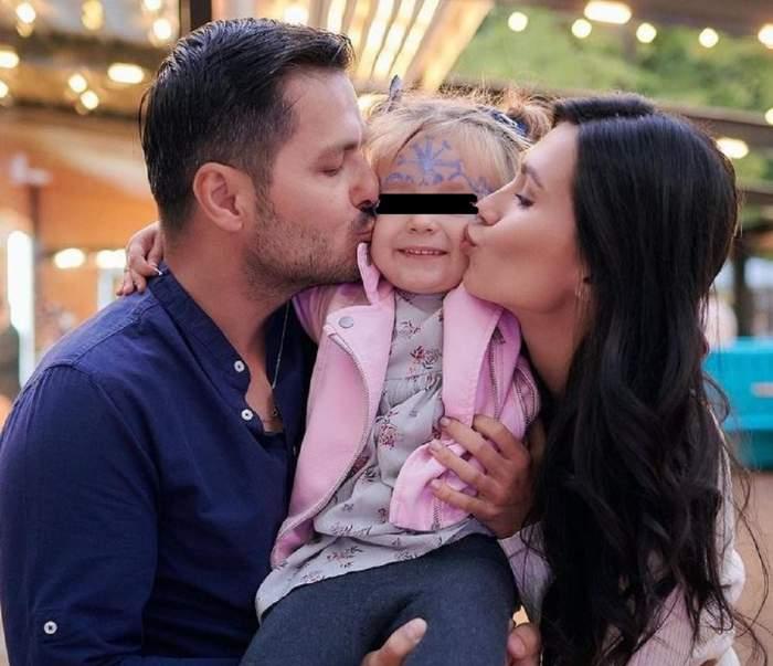 Anda Călin și Liviu Vârciu o țin în brațe pe fetița lor și o sărută pe obraz. Actorul poartă o cămașă albă, partenera lui o bluză albă și fetița o geacă roz, blugi și o bluză înflorată.