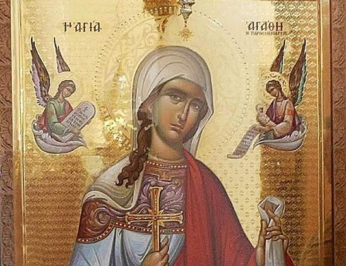 O icoană cu Sfânta Agată. În stânga și în dreapta ei sunt doi îngeri. Ea poartă veșminte colorate în bleu și roșu.