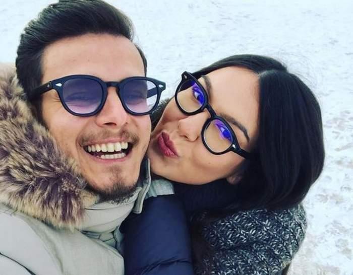 Ionuț Belei și iubita lui se află afară. În spatele lor se poate vedea că pe jos este zăpadă. El zâmbește larg, iar ea își țuguie buzele către el.
