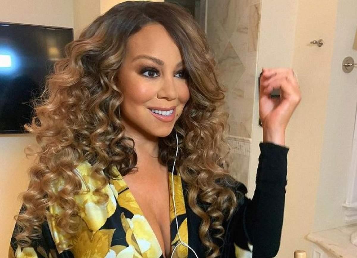 Mariah Carey poartă o bluză neagră, cu motive florale galbene. Vedeta are părul aranjat în bucle.
