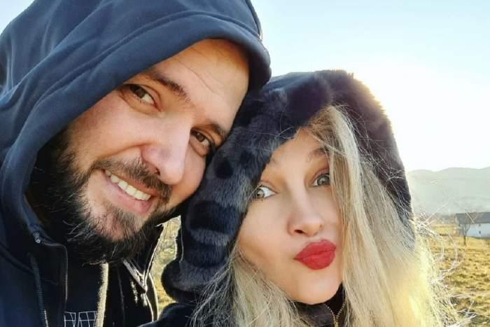 Lora și Ionuț Ghenu se află pe un câmp și își fac selfie. Ea poartă o haină de blană colorată în negru și albastru, iar el un hanorac albastru.