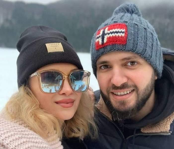 Lora și Ionuț Ghenu își fac un selfie. Cei doi sunt afară. Ea poartă o haină roz și o căciulă neagră, iar el geacă de iarnă și căciulă albastră.