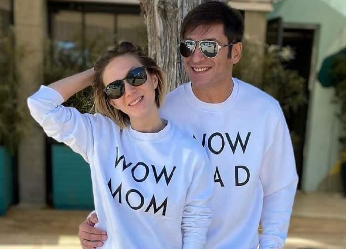 Adela Popescu și Radu Vâlcan poartă ochelari de soare și bluze albe cu scris negru. Amândoi zâmbesc larg.