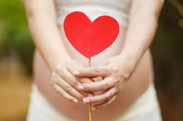O femeie însărcinată ține o inimoară de hârtie în mână. Aceasta poartă fustă albă.