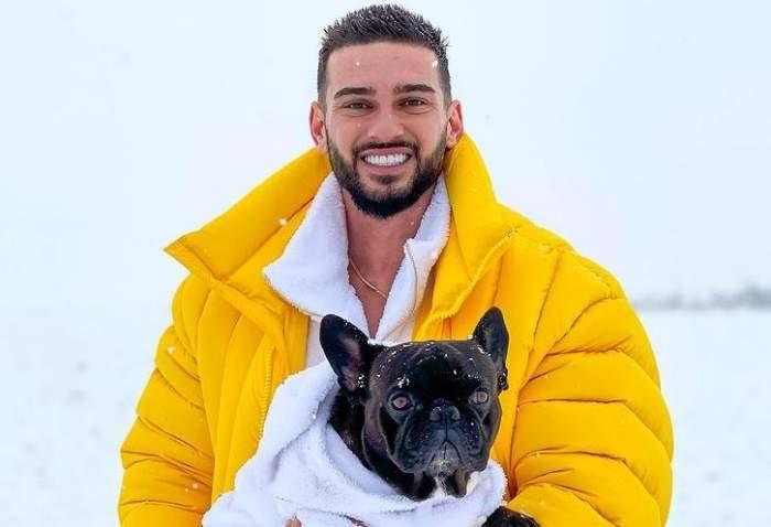 Dorian popa se află afară. Artistul poartă o bluză albă și o geacă galbenă. Cântărețul își ține în brațe câinele negru, pe nume Cheluțu.