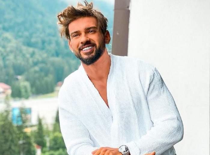 Dorian Popa se află pe un balcon. Artistul poartă un halat alb și zâmbește larg. În spatele lui se văd mai mulți copaci.