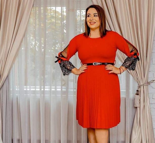 Oana Roman poartă o rochie roșie. Vedeta își ține mâinile în șolduri.