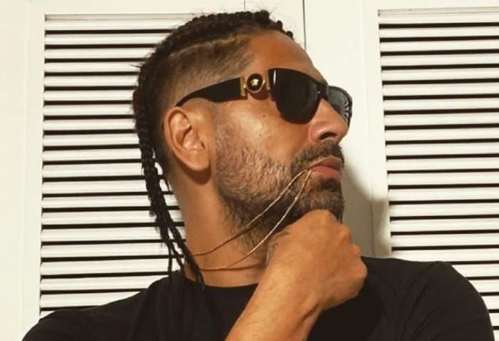 Connect-R poartă ochelari de soare negri și un tricou în aceeași nuanță. Artistul privește într-o parte și are un lanț între buze.
