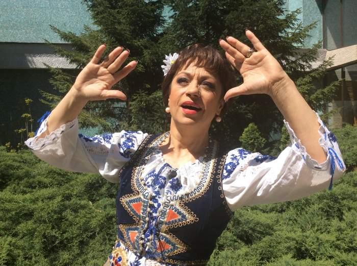 Adriana Trandafir e îmbrăcată cu o ie albă cu model albastru și o vestă neagră. Vedeta are în păr o floare albă.