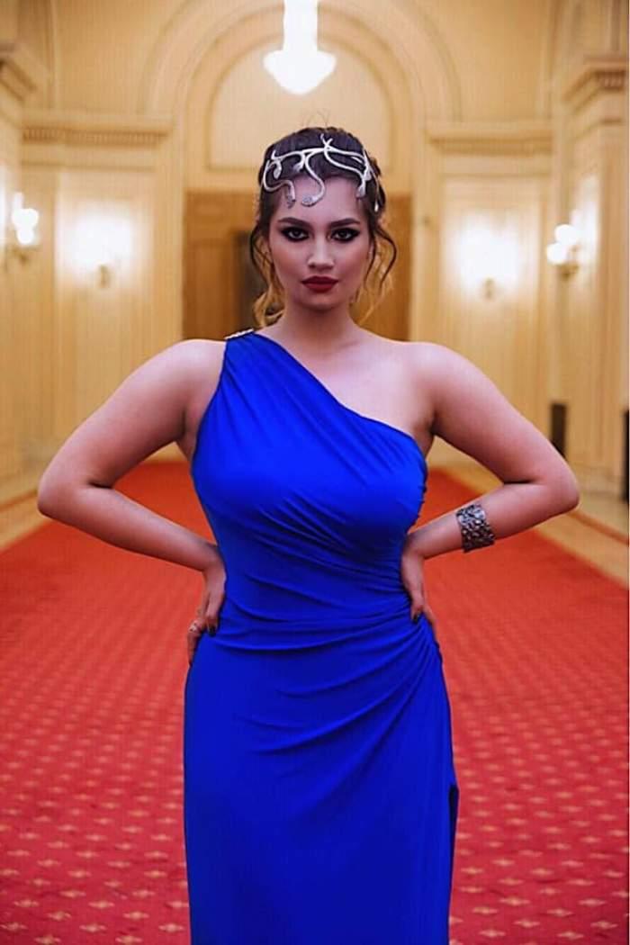 Maria Speranța poartă o rochie albastră. Fiica Adrianei Trandafir ține mâinile în șold.