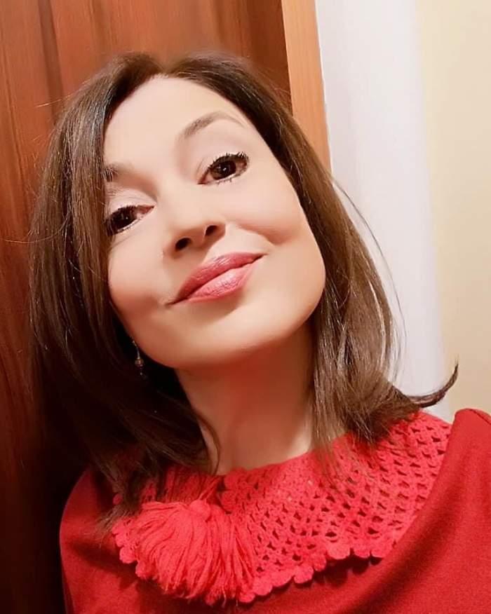 Oana Sîrbu își face un selfie. Vedeta poartă o bluză roșie și zâmbește discret.