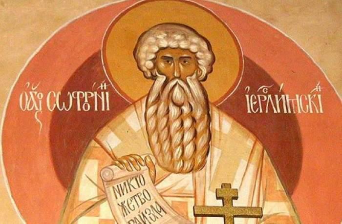 Icoană cu Sfântul Sofronie. Acesta ține o cruce în mână, un pergament și poartă veșminte în nuanțe de crem și oranj.