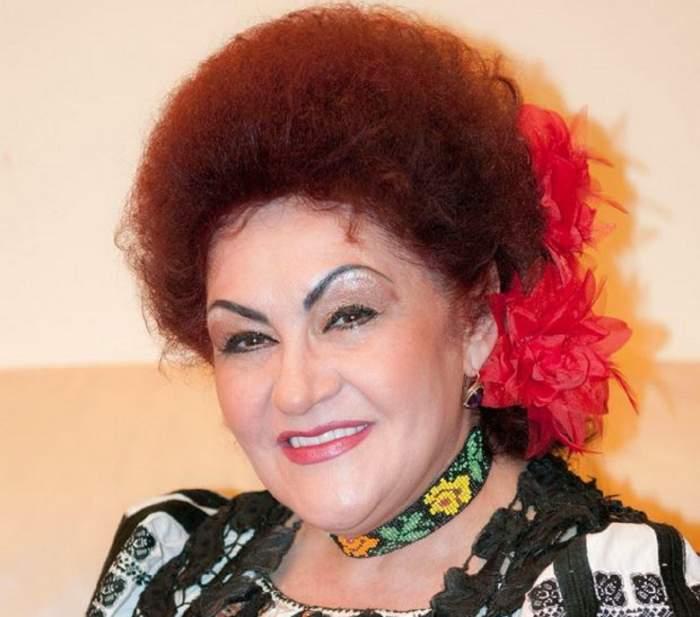 Elena Merișoreanu poartă o ie albă cu model negru și o salbă neagră la gât cu model galben și verde. Artista are în păr o floare roșie.