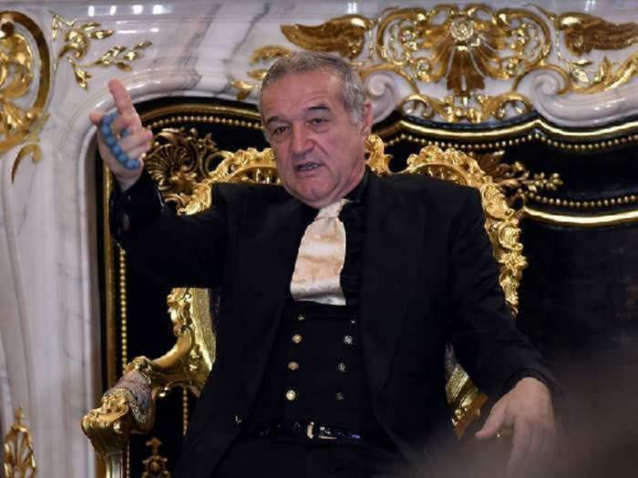 Gigi Becali stă pe un scaun auriu. Milionarul poartă un costum negru cu cravată aurie.