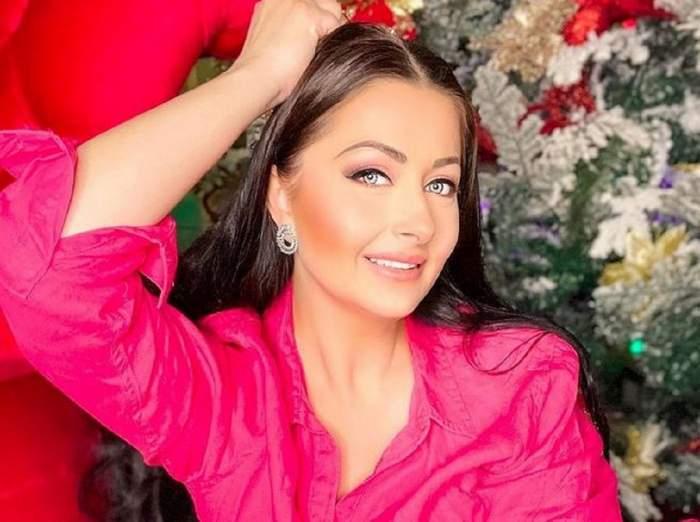 Gabriela Cristea poartă o cămașă roz. Vedeta stă pe un fotoliu roșu și își ține o mână prin păr.