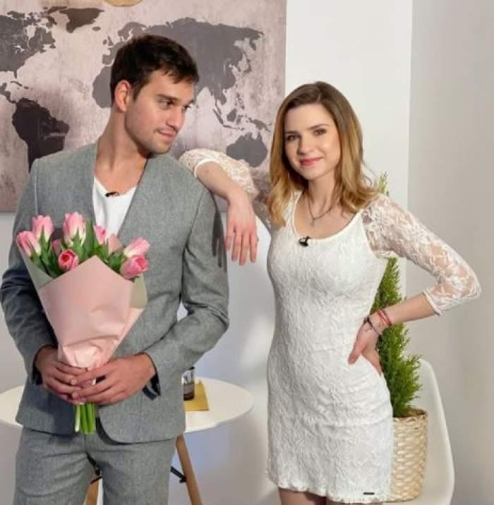 Cristina Ciobănașu în rochie albă și Vlad Gherman cu un buchet roz de lalele în brațe.