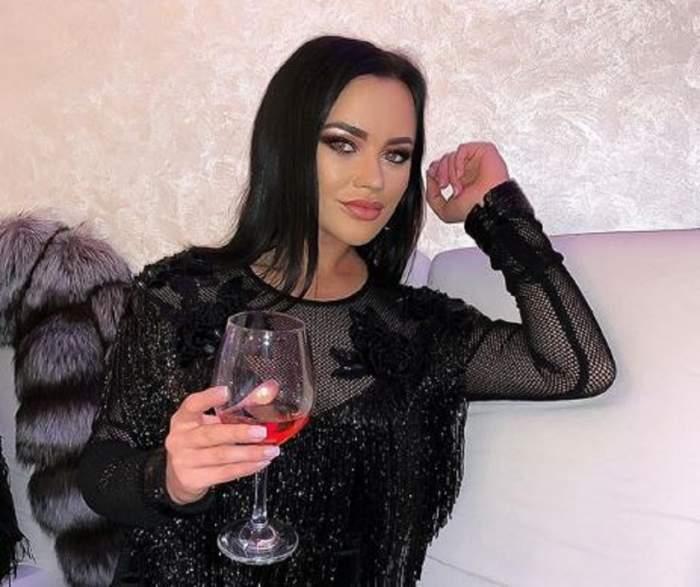Carmen de la Sălciua, în rochie neagră, cu un pahar de vin în mână