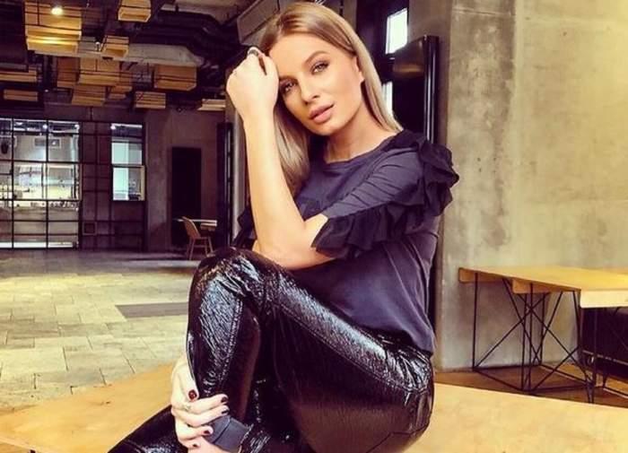 Ana Baniciu poartă un tricou negru și niște pantaloni în aceeași nuanță, lucioși. Vedeta e așezată pe o masă din lemn.