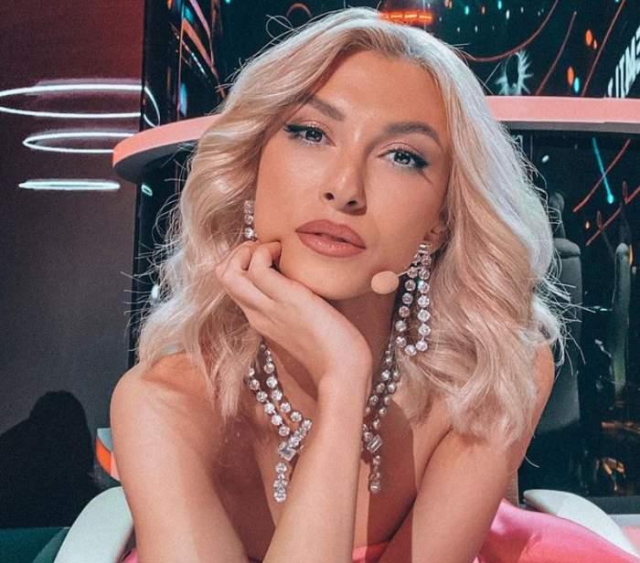 Andreea Balan este la te cunosc de undeva, poarta o rochie cu umeri goi, bijuterii cu pietre si are parul desprins